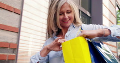 Smiling mature woman walking with shopping bags in town - stock footage