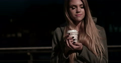 Girl teenager in the street at night drinking coffee and waiting Stock Footage