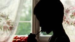 Boy eating Chupa Chups, silhouette Stock Footage