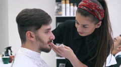 Barber cuts the beard of the client with scissors at a barber shop - stock footage