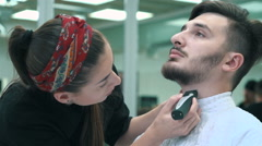Barber cuts the hair of the client with clipper at a barber shop - stock footage