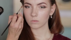 Makeup artist doing a smokey eyes on young beautiful redhead woman Stock Footage