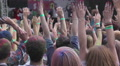 Man throwing paint powder in crowd from stage, people enjoying fest, hands up Footage
