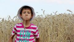Boy in a hat spits in a wheat field Stock Footage