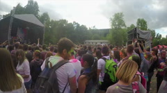 Many young people covered in colorful paint hang out at music fest, slow motion Stock Footage