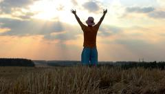 Man raises his hands to heaven in the field rejoices victory, man number one Stock Footage