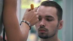 Model is geting ready for photoset by stylist at the barber shop, close up Stock Footage