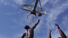 One on one street basketball; low angle looking up at player shooting Stock Footage