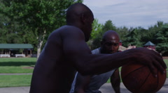 One on one street basketball; closeup on face of player dribbling and shooting Stock Footage