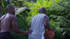 One on one street basketball; long shot of player shooting and scoring Stock Footage