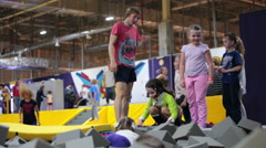 Children with instructor have fun in pit with foam at trampolines Stock Footage
