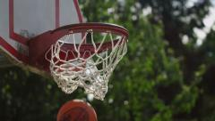 One on one street basketball; closeup of ball going into basket - stock footage