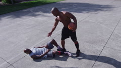 One on one street basketball; player helps rival up off court Stock Footage