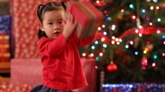 Young girl shaking Christmas gift - stock footage