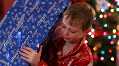 Boy shaking and looking at Christmas gift - stock footage