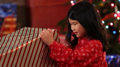 Young girl tearing paper off Christmas present Stock Footage