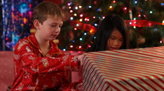 Two kids tear paper off Christmas gifts - stock footage