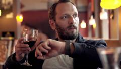 Young impatient man waiting for someone in cafe and drinking wine - stock footage