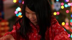 Closeup shot of young girl opening Christmas gift Stock Footage