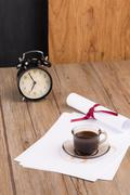 Old clock, hat, coffee and paper sheets Stock Photos