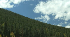 4k POV Moving Driving by mountain full of pine and aspen trees blue sky Stock Footage