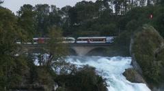 Rhine falls or Rheinfall - Swiss train crosses bridge above impressive waterfall Stock Footage