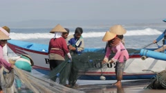 Ladies loading net in fisher boat on beach,Pangandaran,Java,Indonesia Stock Footage