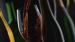 Slow motion shot of red wine pouring with bottles and black background; shot on Stock Footage