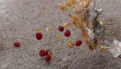 Bowl of cereal and raspberries spilling on carpet in slow motion; shot on - stock footage