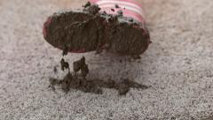 Muddy boot falling onto carpet in slow motion; shot on Phantom Flex 4K at 1000 - stock footage