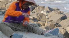 Man fixing fisher net at beach,Pangandaran,Java,Indonesia Stock Footage