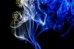Stock Photo of Abstract blue and yellow smoke from the aromatic sticks.