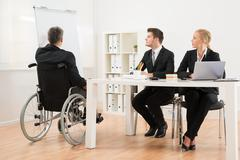 Handicapped Mature Businessman Explaining To His Colleagues In Office Stock Photos