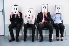 Businesspeople Sitting On Chair Hiding Behind Question Mark Sign - stock photo