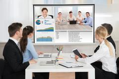 Group Of Businesspeople Attending Video Conference In Office Kuvituskuvat