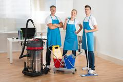 Happy Janitors With Vacuum Cleaner And Cleaning Equipments In Office Stock Photos
