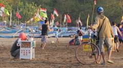 Sellers on beach watch football game,Pangandaran,Java,Indonesia Stock Footage
