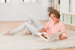Young Woman Sitting On Carpet Looking At Baby's Photo At Home - stock photo