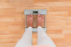 Low Section Of Woman Standing On Weighing Scale Stock Photos