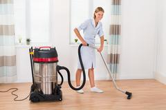 Beautiful Female Maid Cleaning Wooden Floor With Vacuum Cleaner - stock photo
