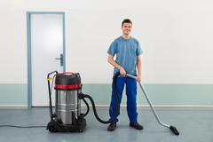 Young Happy Male Worker Cleaning Floor With Vacuum Cleaner Stock Photos