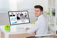Young Happy Businessman Videoconferencing On Computer At Desk Kuvituskuvat