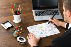 Close-up Of Businessman With Office Supplies And Laptop Drawing Diagram Of St Stock Photos