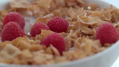 Closeup of raspberries splashing into bowl of cereal in slow motion; shot on Stock Footage