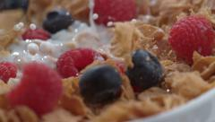 Closeup of raspberries splashing into bowl of cereal in slow motion; shot on - stock footage