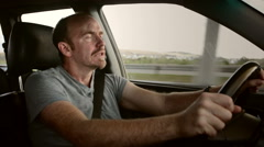 Driver reacts with extreme shock, letting go of steering wheel completely Stock Footage