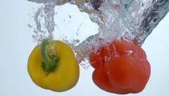 Bell peppers splashing into water in slow motion; shot on Phantom Flex 4K at Stock Footage