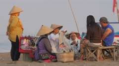 Lady sellers with conical hat and tourists,Pangandaran,Java,Indonesia - stock footage