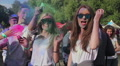 Guys spraying colorful powder over pretty girls, happy friends hang out at event Footage