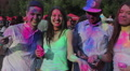 Happy young people covered in colorful paint throwing color powder, laughing Footage